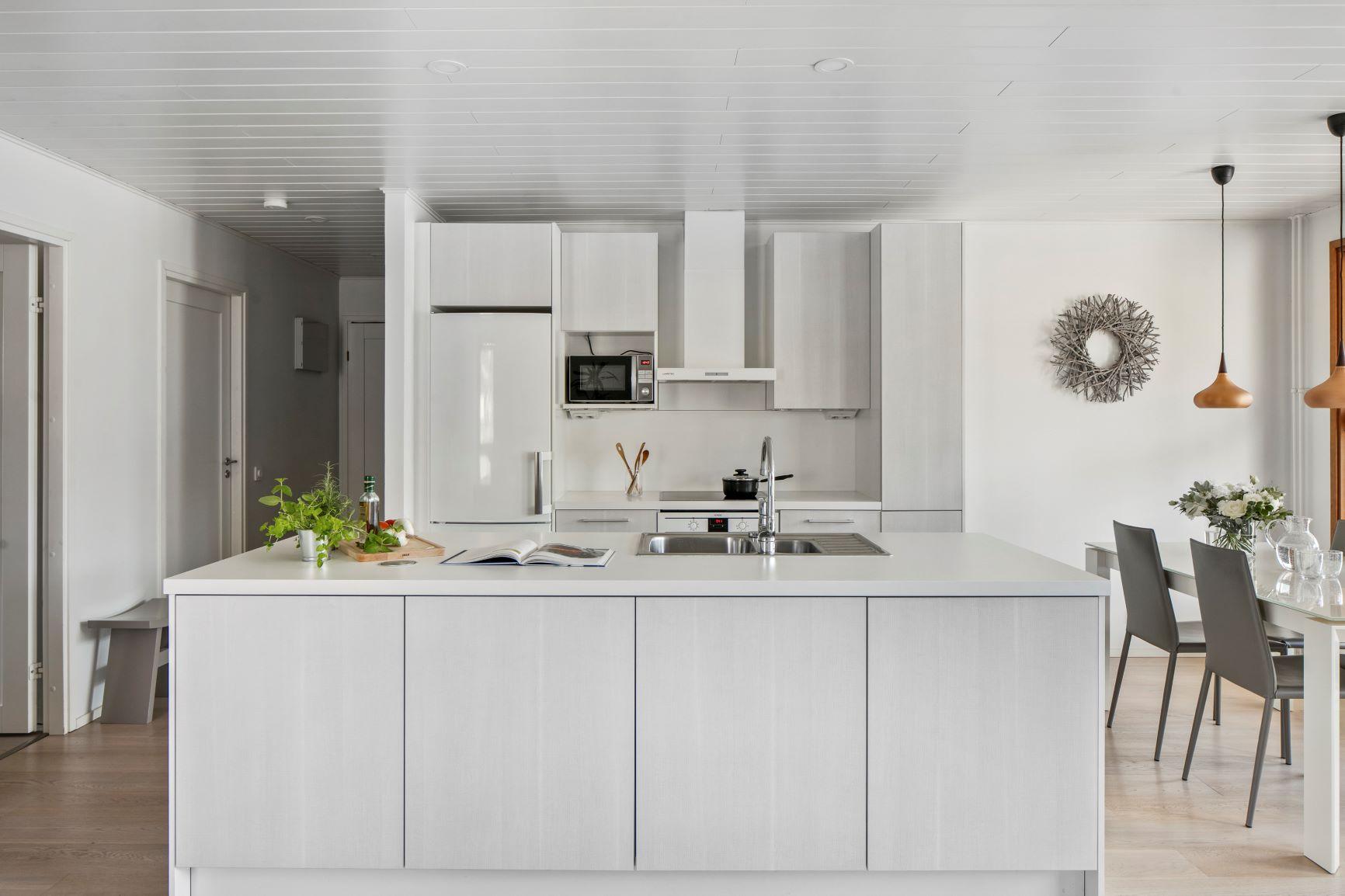 Valkoinen moderni keittiö suurella saarekkeella